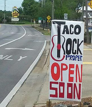 Sign reads: Taco Rock Proper Open Soon