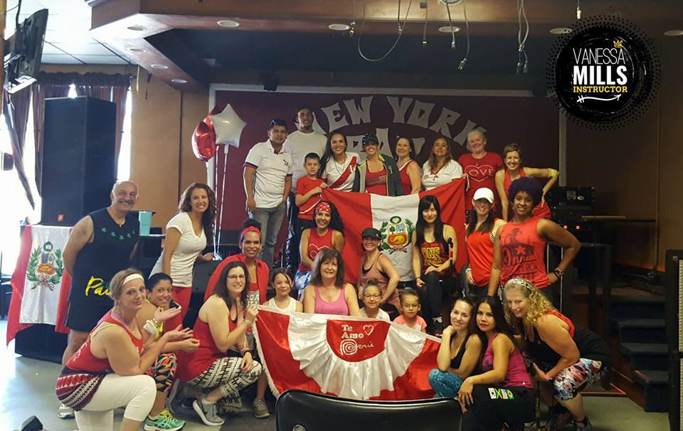 Participants of zumbathon pose for photo with Peruvian flag