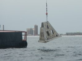 artificial reef modules being dropped into water with crane
