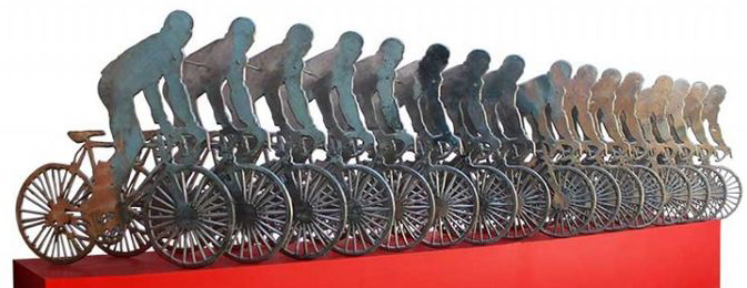 Art display of a row of bicicles on a red block