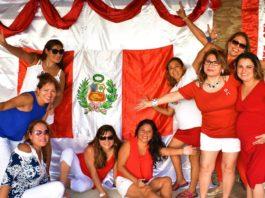 Gropu of women standing next to a Peruvian flag