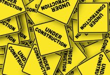 """yellow caution signs that say """"under construction"""""""