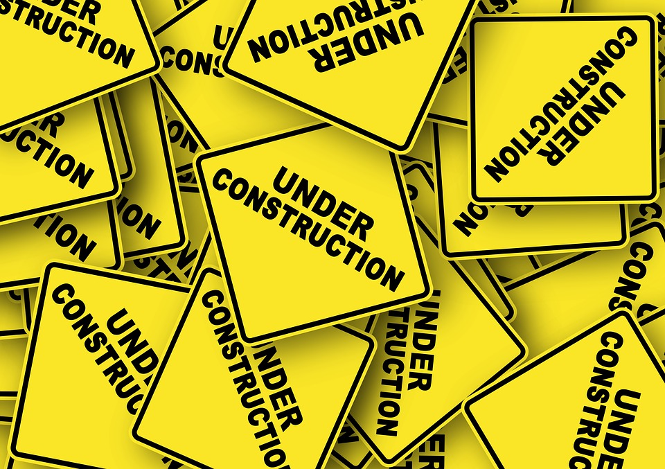 "yellow caution signs that say ""under construction"""
