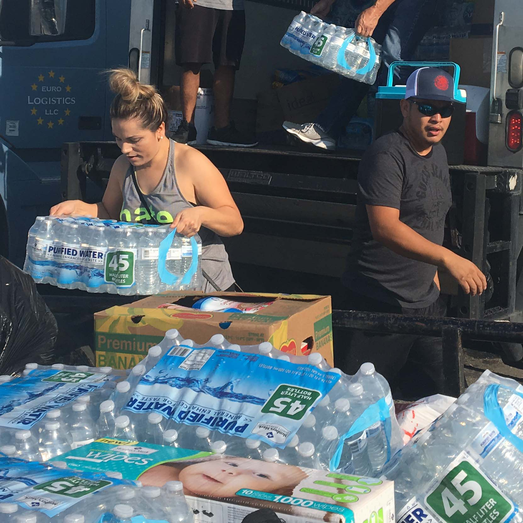 volunteers load truck with bottled water