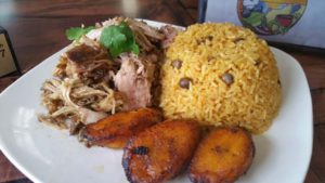 pulled pork, rice and fried plantains on a plate