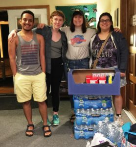 Donors stand with cases of donated water bottles