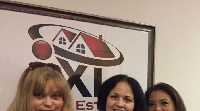 three women standing in front of iXL Real Estate sign