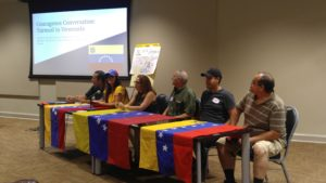 Venezuelan nationals sitting behind tables drapped with the Venezuelan flag