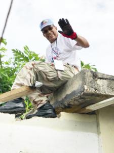 Man repairing roof and waving to camera