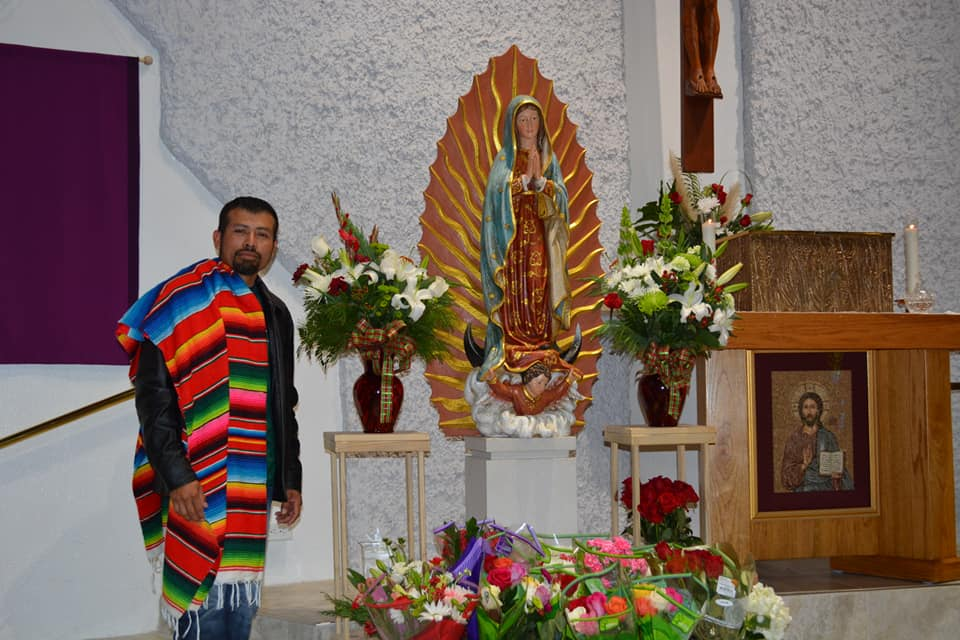 man posing with statue of virgen de guadalupe