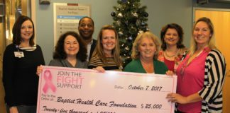 seven people holding large pink check