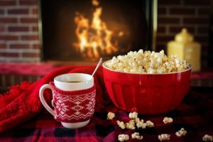hot chocolate, popcorn on a table in front of a burning fireplace