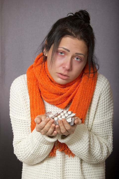 woman with flu holding pills
