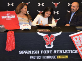 Athlete signs contract with Spanish Fort Athletics docorated table and backdrop, parents at side