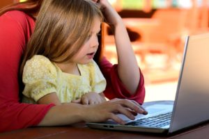 little girl sitting on woman's lap using a laptop computer