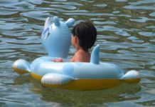 Child sitting on inflatable toy floating in the water