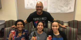 "man wearing shirt that says ""puerto rico"" standing behind three teen girls seated at a table holding sodas"