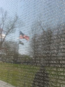Names engraved into Vietname Memorial Wall with reflection of American flag