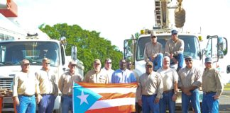 Nine electric company employees standing in front of utility trucks holding a puerto rican flag