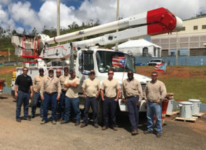 Nine employees of the electric company standing in front of a bucket truck