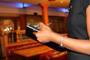 hands of server writing restaurant orderq