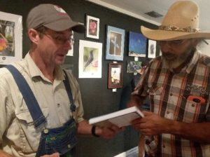 A man hands a book to another man