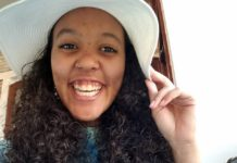 Young woman smiling wearing a floppy hat