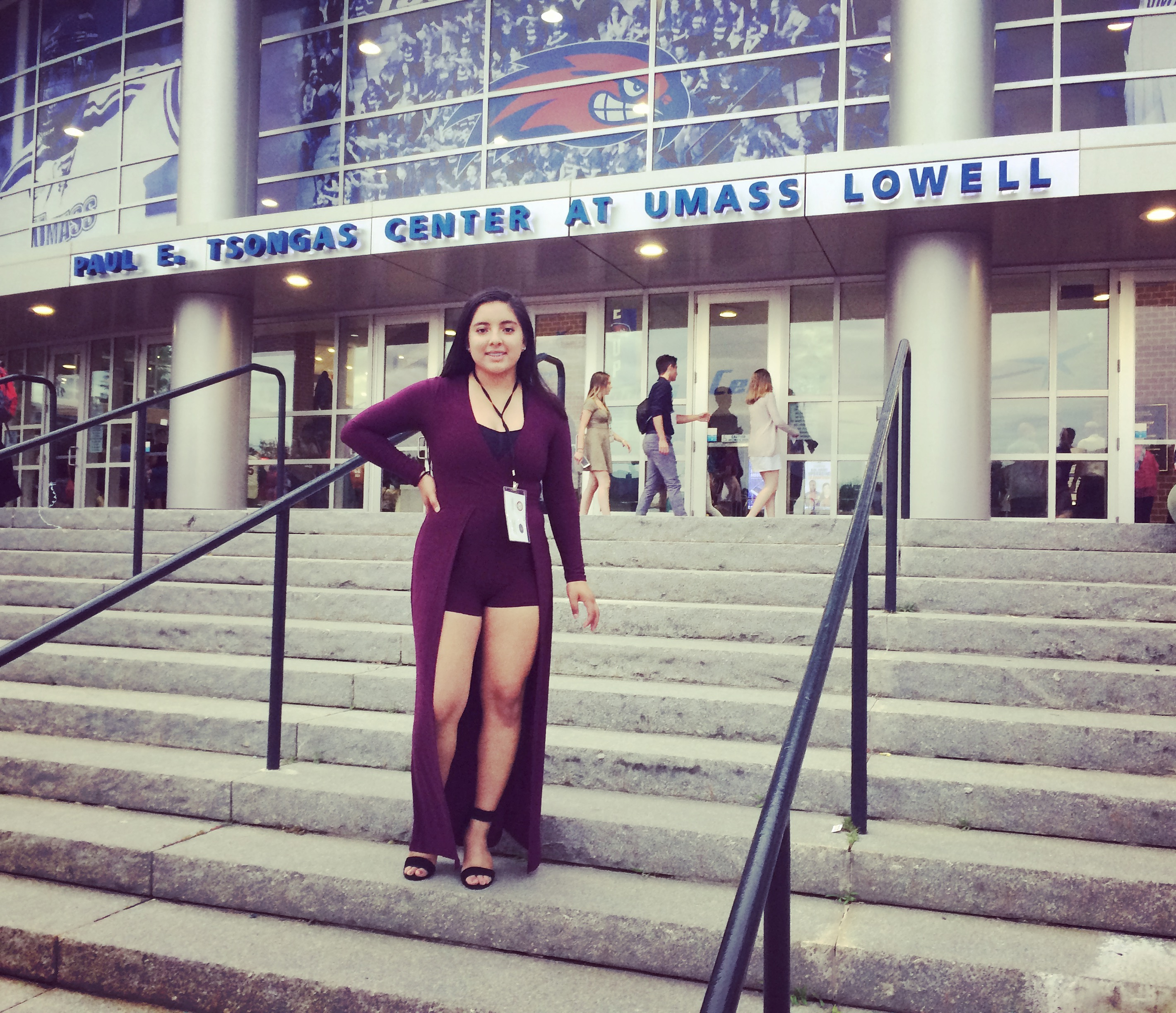 young woman standing on steps in front of UMASS Lowell Center