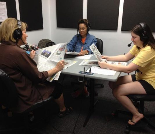 three women sitting in a recording studio wearing headphones and reading newspapers