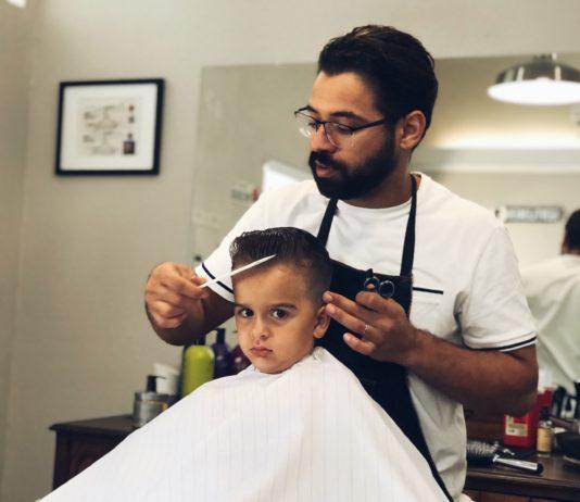 barber cutting boy's hair