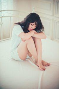 girl on bed hugging her legs