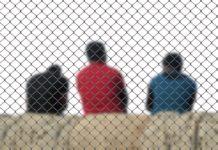 three men sitting inside a fence