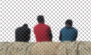 three men sitting inside a fence