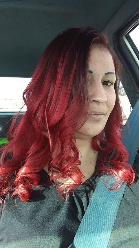 woman with long red hair siting in car