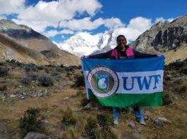 girl holding UWF flag on top of mountain