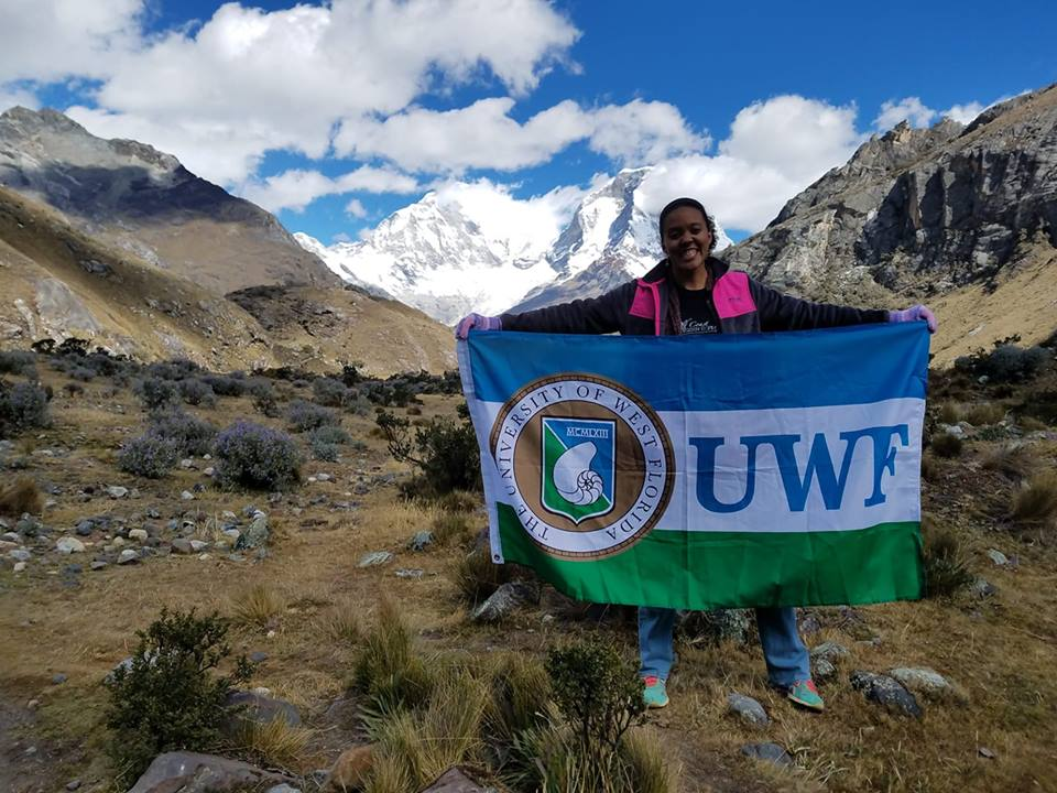 girl holding UWF flag on top of mountain