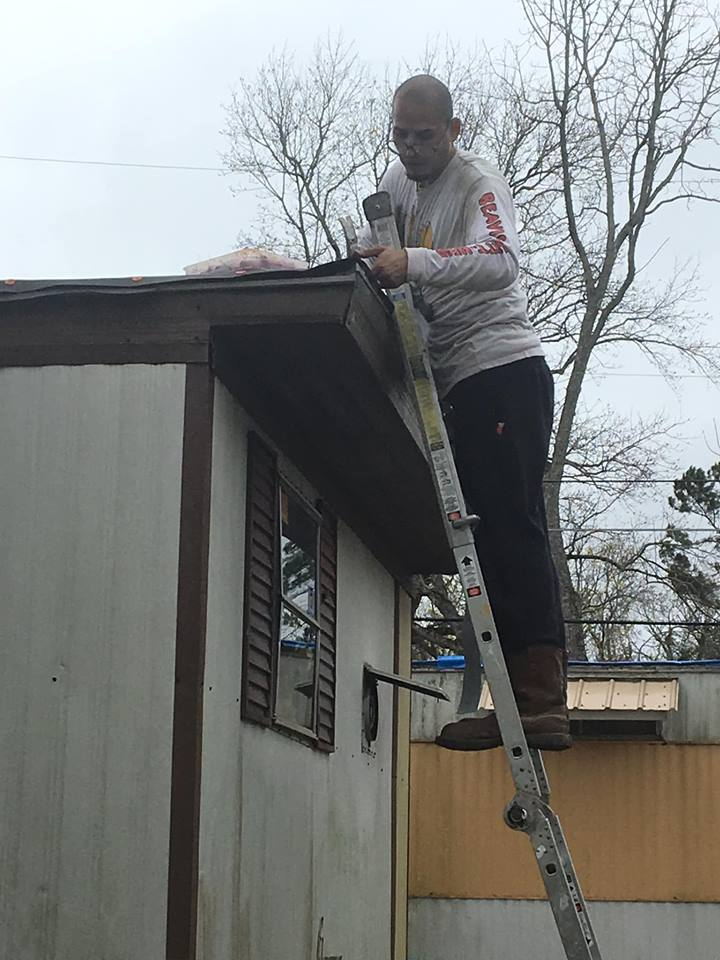 Man standing on ladder repairing roof