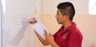 Teen boy writing on marker board
