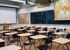 classroom with tables, chairs and blackboard