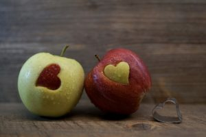 two apples with hearts cut into them