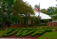 Letters UWF shaped hedges below three flagpoles.