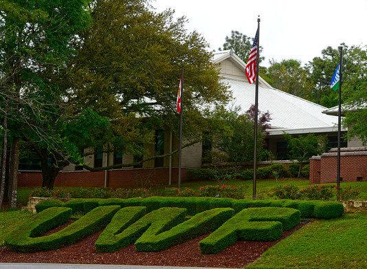 Letters UWF shaped hedges below three flagpoles.