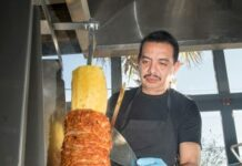 restaurant worker cutting meat and pineapple on from a vertical rotisserie