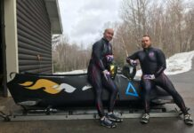 two people leaning on a bobsled