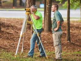 two men using construction surveying equipment