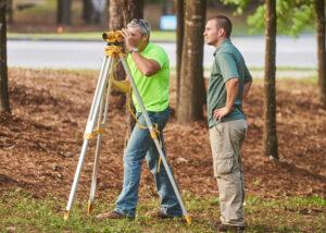 two men using construction surveying equipment