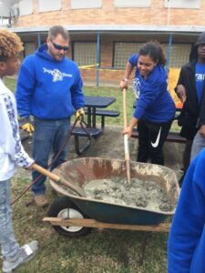 students are being taught how to mix cement in a wheelbarrow
