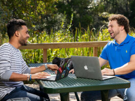 two people sitting at an outdoor table smiling with laptops between them