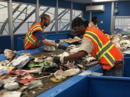 Two men sorting through garbage on a conveyor belt
