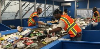 Two men sorting through garbage on a conveyor belt